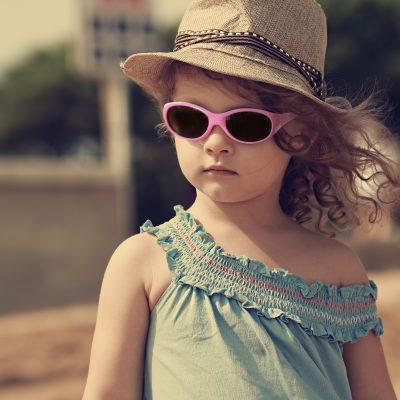 barn i solglasögon och hatt